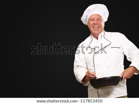 Male Chef Stirring A Non Stick Pan On A Black Background - stock photo