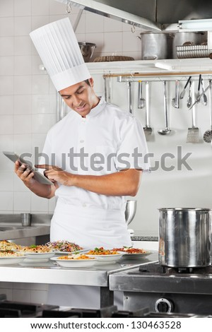 Male chef using digital tablet with pasta dishes at commercial kitchen counter - stock photo