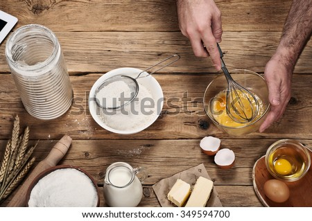 Male chef whipping eggs in the bakery on wooden table. Ingredients for cooking flour products or dough  (flour, eggs, milk, butter). Top view - stock photo