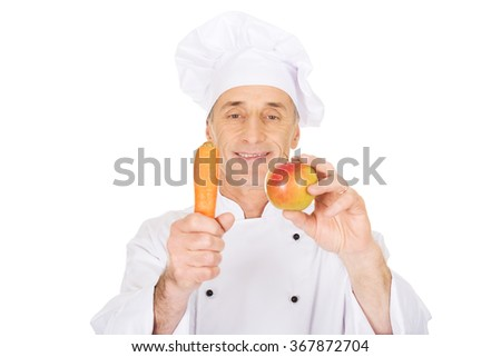 Male chef with an apple and carrot - stock photo