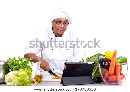 Male chef with fruits and vegetables and tablet for recipe - stock photo