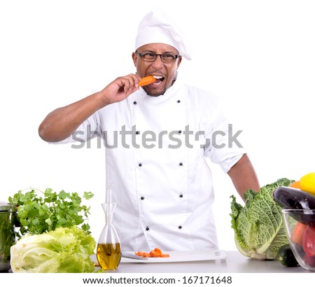 Male chef with fruits and vegetables eating a carrot - stock photo