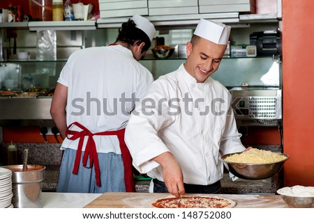 Male chefs working in kitchen, back-office shot - stock photo