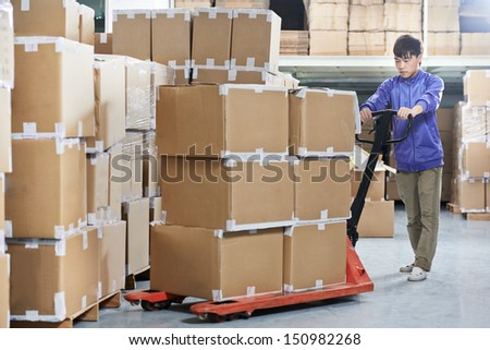Male chinese worker with fork pallet truck stacker in warehouse loading group of boxes packages - stock photo