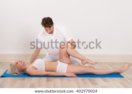 Male Chiropractor Doing Physio Therapy For Female Patient - stock photo