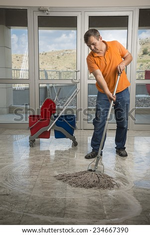 Male cleaner with mop and uniform cleaning hall floor. - stock photo