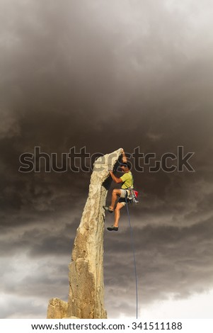 Male climber dangles from a sheer rock spire. - stock photo