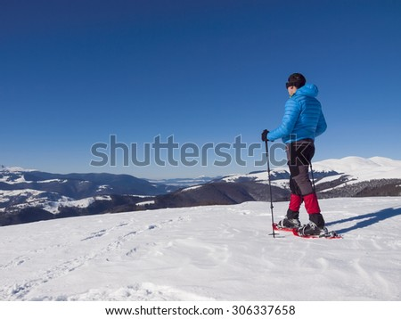 Male climbers in snowshoes and goes on soft snow in the mountains.