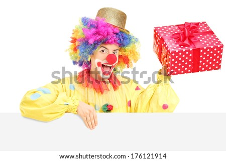 Male clown with cheerful expression holding a present behind blank panel isolated on white background - stock photo