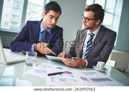 Male colleagues discussing new project or data in office