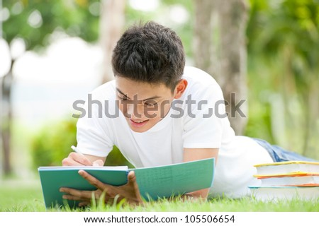 Male college student lying on the grass and writing in notebook - stock photo