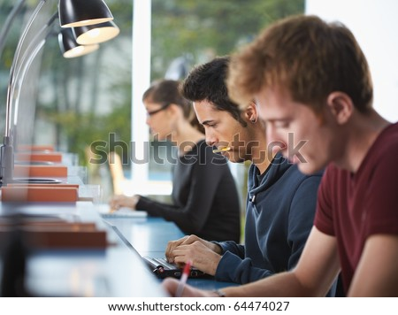 male college student sitting in library, typing on laptop computer. Horizontal shape, side view, waist up - stock photo