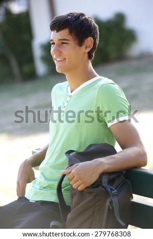 Male College Student Sitting On Bench With Backpack - stock photo