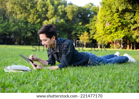 male college student use tablet lying on the park - stock photo