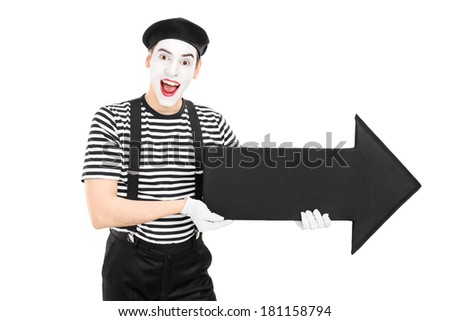 Male comedian holding a big black arrow pointing right isolated on white background - stock photo