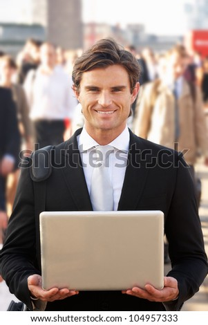 Male commuter in crowd using laptop