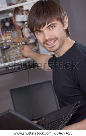male computer technician with laptop in his hand repairing computer - stock photo