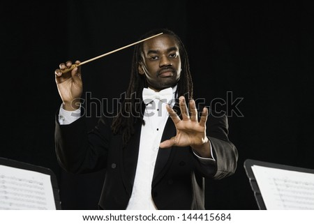 Male conductor holding baton - stock photo