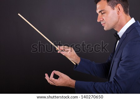 male conductor with eyes closed on black background - stock photo