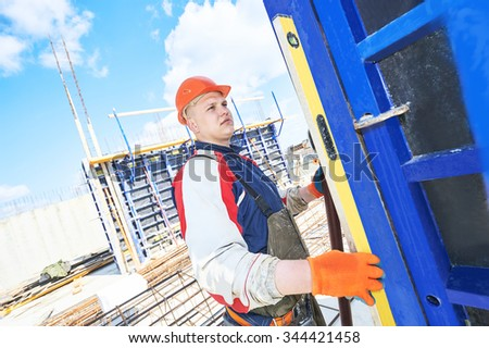 Male construction builder worker with bubble level at building site