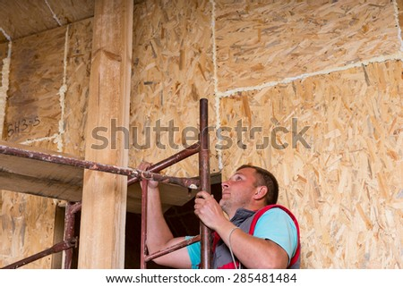 Male Construction Worker Builder Looking Scared While Climbing Up Ladder of Scaffolding Inside Unfinished Home with Exposed Particle Plywood Boards Frame - stock photo