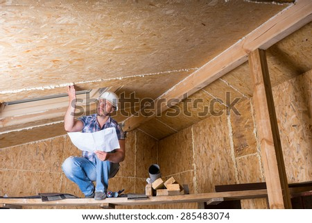Male Construction Worker Builder Wearing White Hard Hat Crouching on Elevated Scaffolding and Reading Plans near Ceiling of Unfinished Home with Exposed Plywood Particle Board - stock photo