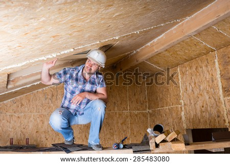 Male Construction Worker Builder Wearing White Hard Hat Crouching on Elevated Scaffolding near Ceiling in Unfinished House with Exposed Particle Plywood Board - stock photo
