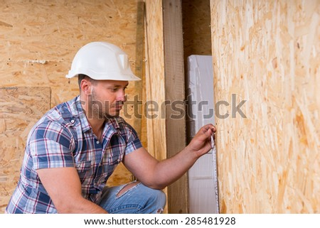 Male Construction Worker Builder Wearing White Hard Hat Measuring Door Frame with Tape Measure Inside Unfinished Home with Exposed Particle Plywood Boards - stock photo