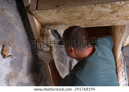 Male Construction Worker Builder with Cordless Drill Building Frame for Stairs in Basement of Unfinished Home with Exposed Cement Wall - stock photo