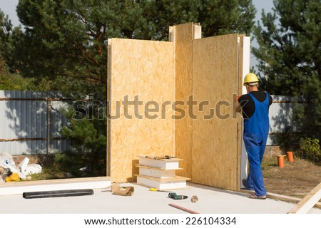 Male Construction Worker Building a Real Estate House Wall Alone. - stock photo
