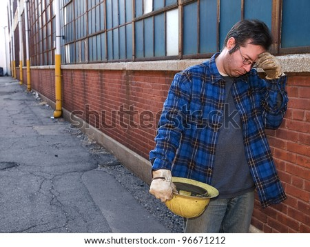 Male Construction Worker, forlorn, outdoors, out of work in alley - stock photo