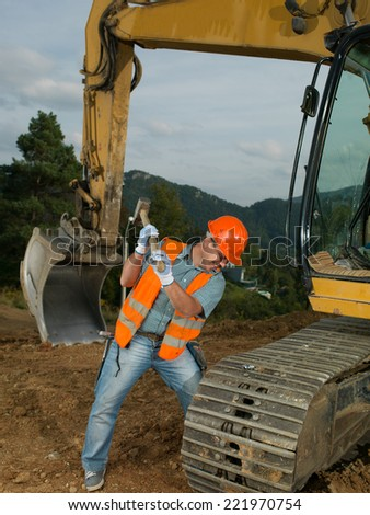 male construction worker repairing excavator track  - stock photo
