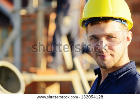 Male construction worker smiling at a building site - stock photo