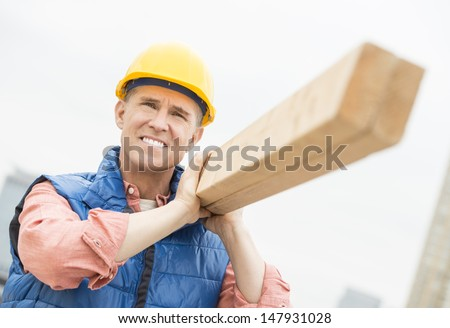 Male construction worker smiling while carrying wooden plank on shoulder - stock photo