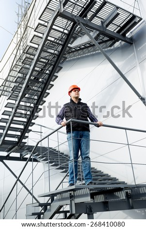 Male construction worker standing on steel staircase at factory - stock photo