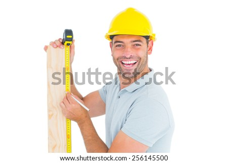 Male construction worker using measure tape to mark on wooden plank on white background