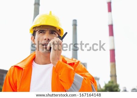 Male construction worker wearing reflective workwear communicating on two way radio at site - stock photo