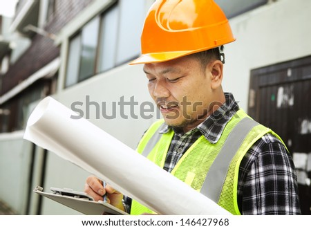 Male construction worker wearing safety vest at a building site - stock photo
