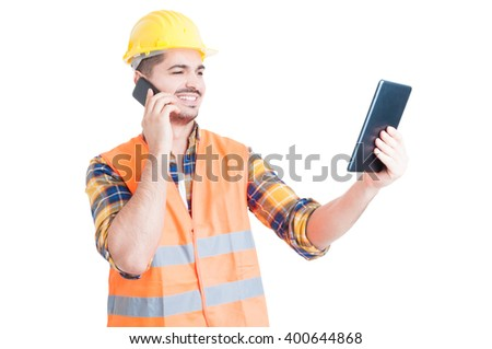 Male constructor in workwear with modern tablet using cell phone and smiling on white studio background - stock photo
