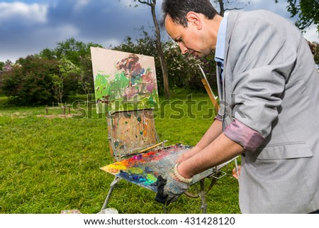 Male contemplative artist cleaning off his palette ona sketchbook after painting during an art class in a park - stock photo