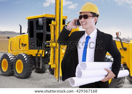 Male contractor holding blueprint while talking on the phone with the road construction machine, shot on the road