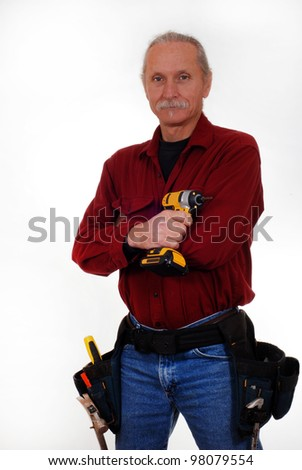 Male contractor holding cordless drill, wearing tool belt - stock photo