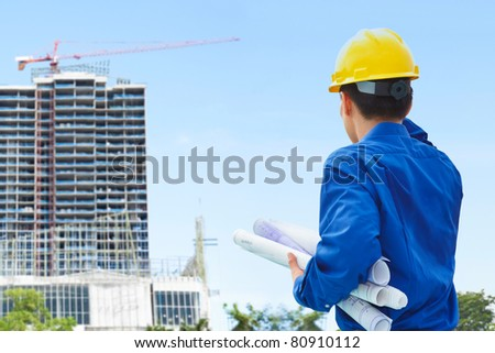Male contractor or civil engineer looking at the building project on progress