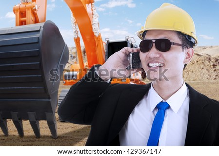 Male contractor talking on the mobile phone with an excavator on the background, shot outdoors