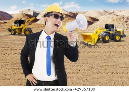 Male contractor using a megaphone for yelling with an excavator and backhoe on the background - stock photo