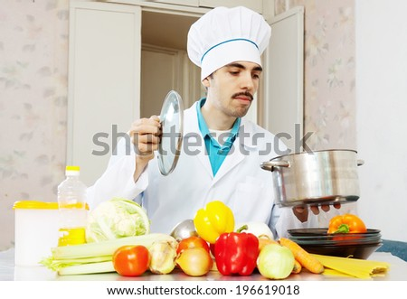 Male cook in uniform cooking with vegetables in kitchen - stock photo