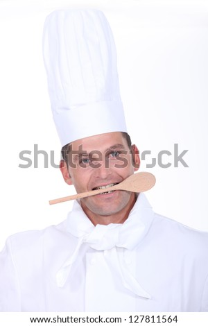 male cook with a wooden spoon in the mouth - stock photo