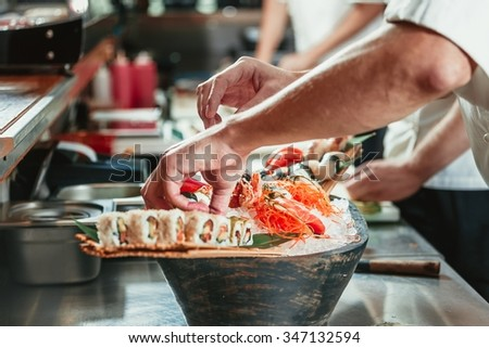 male cooks preparing sushi in the restaurant kitchen - stock photo