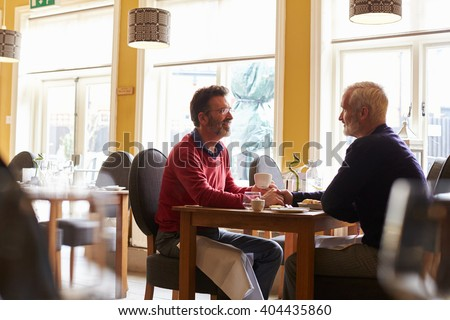 Male couple hold hands at a restaurant, three quarter length - stock photo