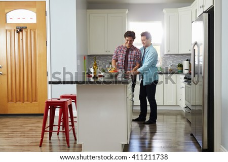 Male couple in the kitchen preparing a meal, looking down - stock photo